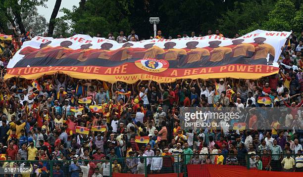 East Bengal supporters wave a club banner as they celebrateduring an I-League football match at The Kanchenjungha Stadium in Siliguri on April 2,...