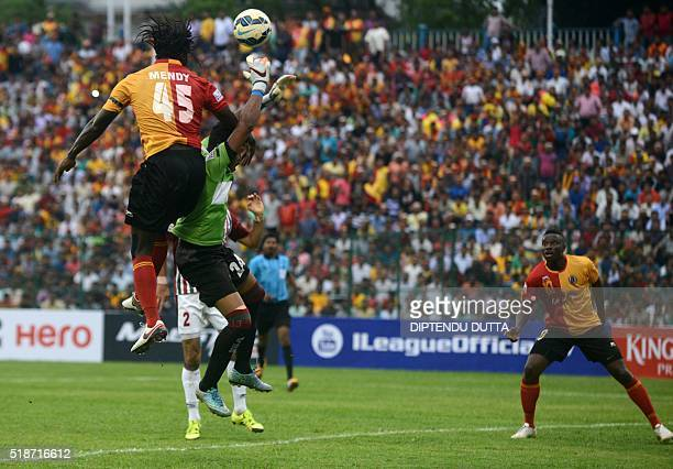 East Bengal's Bernerd Mendyfights for the ball with Mohun Bagan's goalkeeper Debjit Majumder during an ILeague football match at The Kanchenjungha...