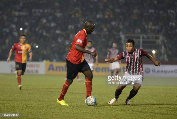 East Bengal's Ivan Bukenya controls the ball past Mohun Bagan's Jeje Lalpekhlua during an Indian ILeague football match between Mohun Bagan and East...