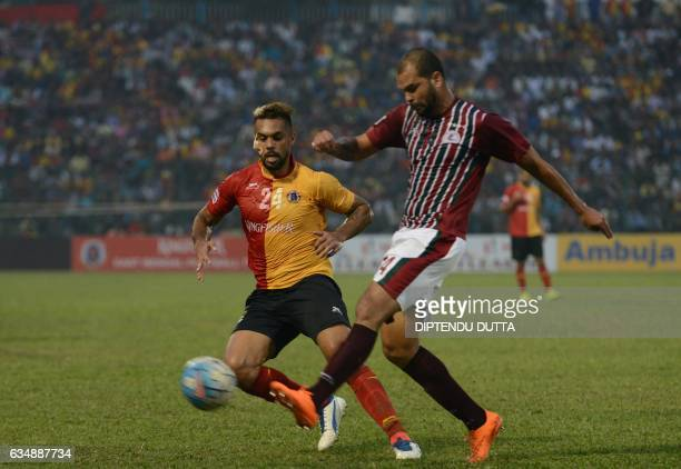 East Bengal's Robin Singh is tackled by Mohun Bagan's Eduardo Soares Ferreira during an Indian ILeague football match between Mohun Bagan and East...