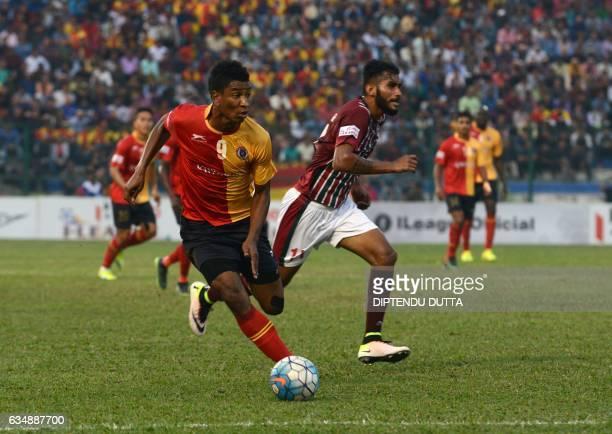 East Bengal's Willis Deon Plaza is tackled by Mohun Bagan's Subhasish Bose during an Indian ILeague football match between Mohun Bagan and East...