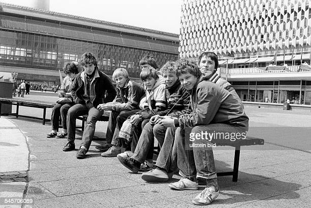 GDR East Berlin Mitte Teenagers at Alexanderplatz in the background the department store Centrum Warenhaus and the interurban railway station...