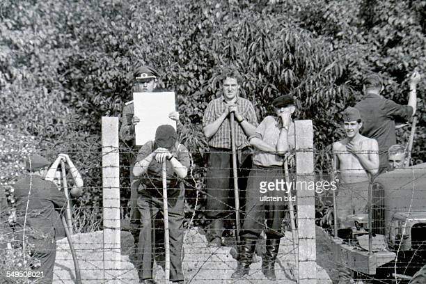 East Berlin policeman is trying to blind someone on the West Berlin side who is taking a picture of reinforcement works on the sector border at the...