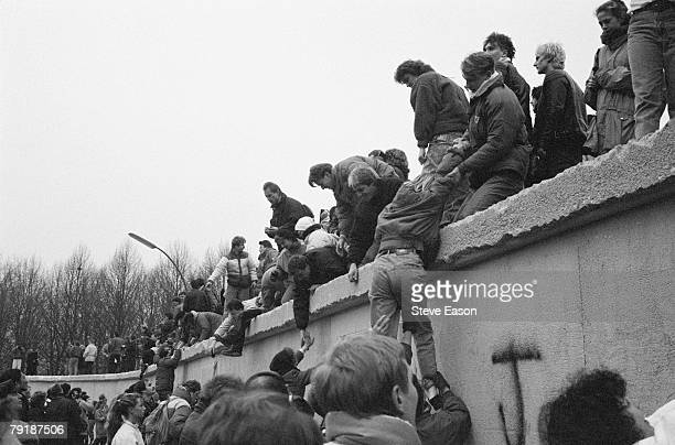 East Berliners climb onto the Berlin Wall to celebrate the effective end of the city's partition 31st December 1989