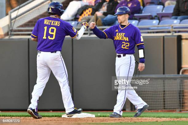 East Carolina assistant coach Jeff Palumbo congratulates East Carolina catcher Travis Watkins after a single in a game between the St Johns Red Storm...