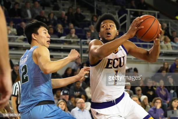 East Carolina Pirates forward Jayden Gardner drives to the basket while guarded by Tulane Green Wave guard Kevin Zhang during a game between the East...