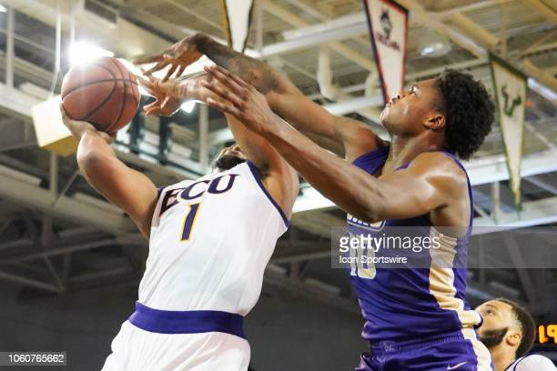 East Carolina Pirates forward Jayden Gardner is fouled by James Madison Dukes forward Greg Jones during a game between the East Carolina Pirates and...