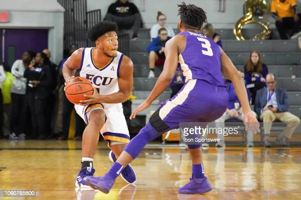 East Carolina Pirates forward Jayden Gardner looks for a pass while being defended by James Madison Dukes guard Stuckey Mosley during a game between...
