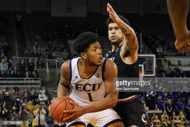 East Carolina Pirates forward Jayden Gardner looks to pass the ball while being guarded by Cincinnati Bearcats guard Jarron Cumberland during a game...