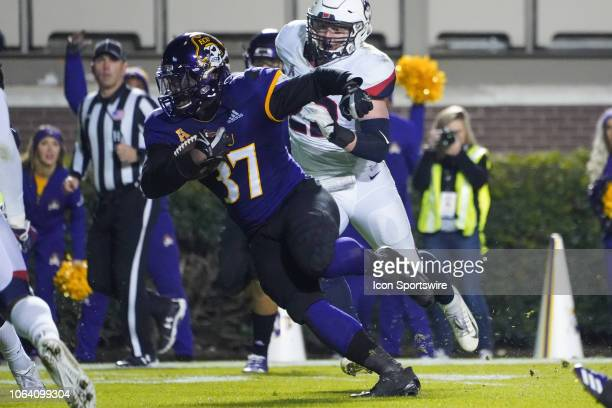 East Carolina Pirates linebacker Xavier Smith catches a pass and runs with the ball during a game between the UConn Huskies and the East Carolina...