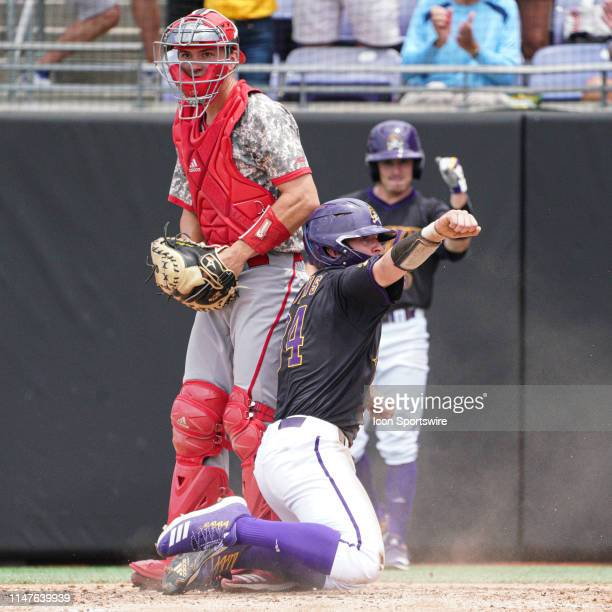 East Carolina Pirates outfielder Chandler Jenkins reacts after scoring in front of North Carolina State Wolfpack catcher Patrick Bailey during a game...