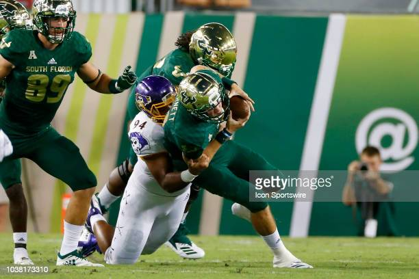 East Carolina's Alex Turner wraps up South Florida's quarterback Blake Bennett during the College Football game between the ECU Pirates and the South...