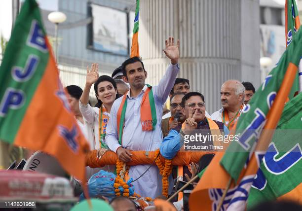 East Delhi candidate for Lok sabha elections Gautam Gambhir and his wife Natasha Jain wave at the crowd during a roadshow ahead of the sixth phase of...