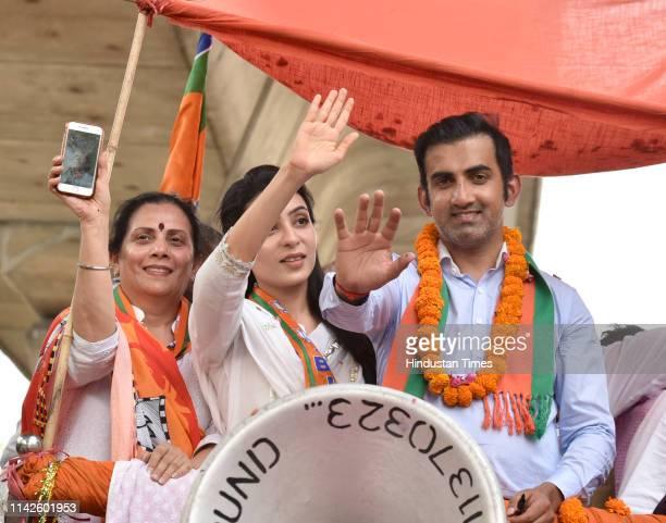 East Delhi candidate for Lok sabha elections Gautam Gambhir his wife Natasha Jain and mother Seema Gambhir wave at the crowd during a roadshow ahead...