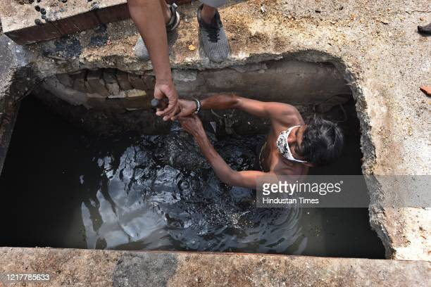 East Delhi Municipal Corporation sanitation workers manually cleaning drains near the Ganesh Nagar Mother Dairy plant, on June 5, 2020 in New Delhi,...