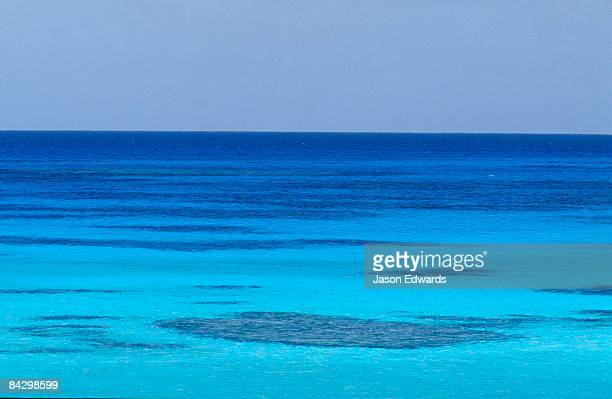 rich turquoise seas and coral reefs surround remote tropical islands. - coral sea stock photos and pictures
