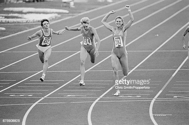 East German athlete Katrin Krabbe competing for the German Democratic Republic throws her arms in the air in celebration as she crosses the finish...