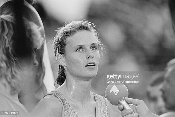 East German athlete Katrin Krabbe competing for the German Democratic Republic is interviewed by reporters after finishing in first place ahead of...