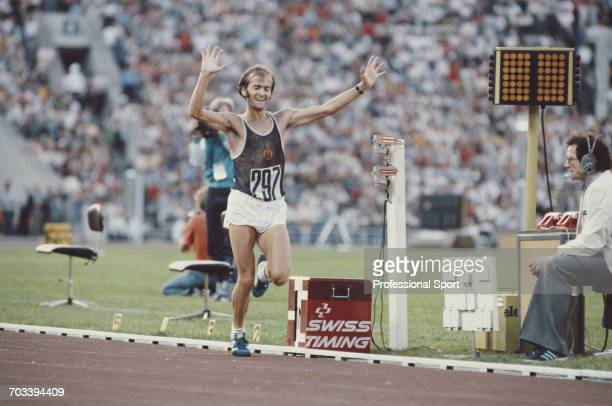 East German athlete Waldemar Cierpinski of the East Germany team celebrates as he crosses the finish line in first place to win the gold medal in the...