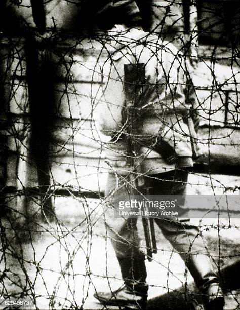 East German Border Guard Viewed Through Barbed Wire Fence 1965