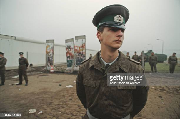 East German border guards in the former 'death strip' on the Eastern side of the Berlin Wall, where it divided Potsdamer Platz, after several...