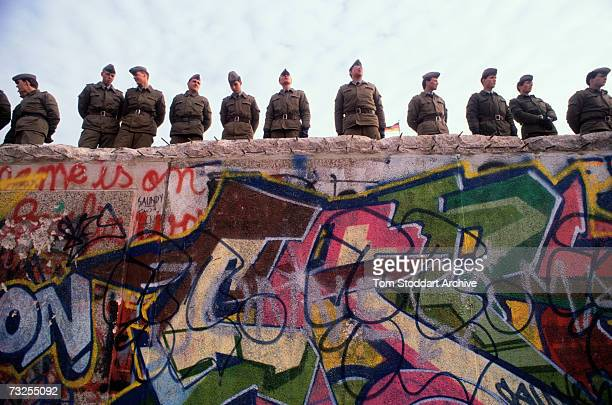 East German border guards on top of the Berlin Wall on the morning of 10th November 1989 while elsewhere the first section of the wall is being torn...