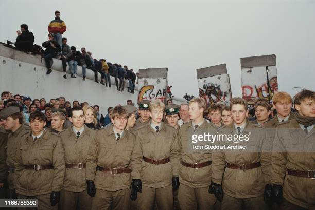 East German border guards stand in line in the former 'death strip' on the Eastern side of the Berlin Wall where it divided Potsdamer Platz after...
