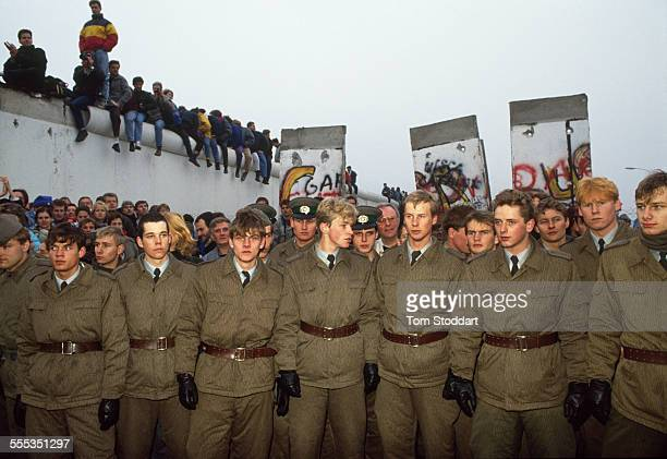 East German border guards stand in line after several sections of the Berlin Wall have been removed by jubilant crowds on the morning of November 10...