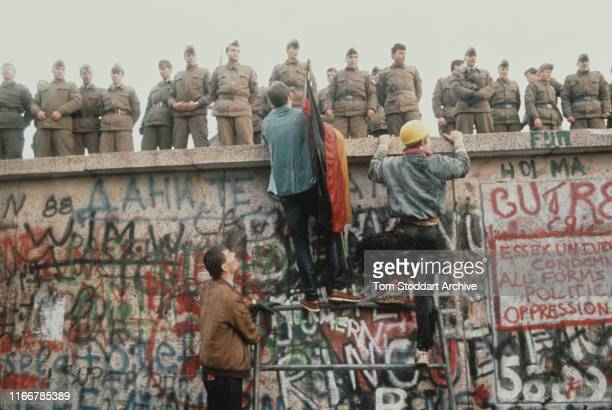 East German border guards stand in line on the Berlin Wall as as West Berliners with a German flag scale the wall on the morning of 10th November...
