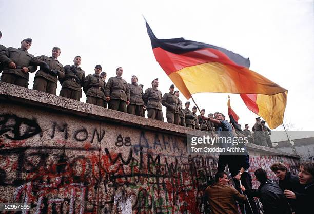 East German border guards try to prevent a crowd climbing onto the Berlin Wall on the morning that the first section was pulled down This is a...