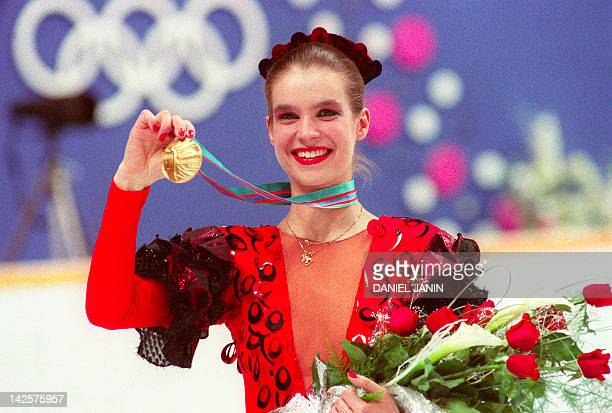 East German figure skater Katarina Witt smiles as she displays her gold medal 27 February 1988 at the Olympic Saddledome in Calgary Katarina Witt...