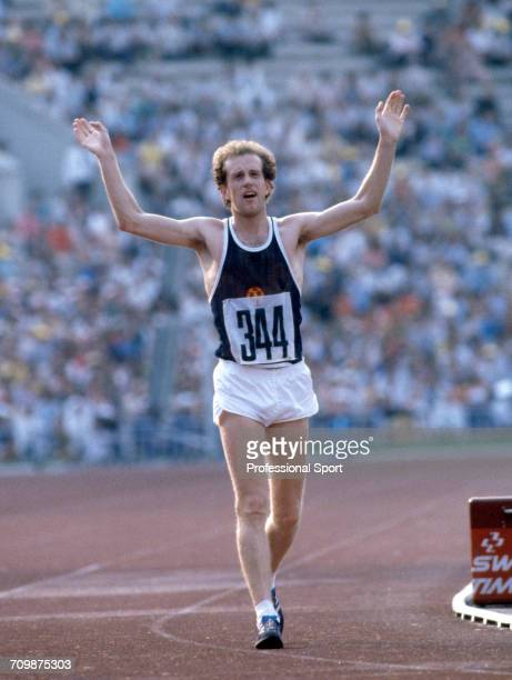 East German race walker Roland Wieser raises his arms in the air in celebration as he crosses the finish line in third place to win the bronze medal...