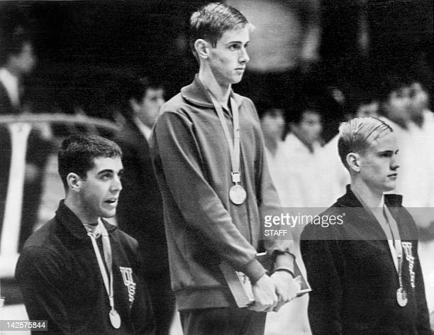 East German Roland Matthes winner of the gold medal in the 200m backstroke listens to the national anthem flanked by silver medalist Mitchell Ivey...