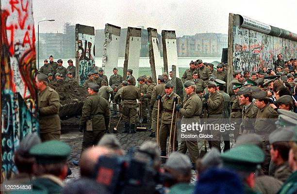 East German soldiers and West German soldiers remove some of the first sections of the Berlin Wall at Potsdammer Platz