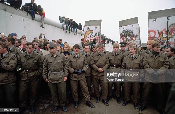 East German soldiers stand by as the Berlin Wall is dismantled
