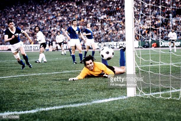 East Germany goalkeeper Jurgen Croy watches in anguish as the ball evades his dive and hits the post before rebounding to safety East Germany captain...