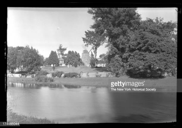 East Hampton, Long Island: view across East Hampton Town Pond to South-End burial ground cemetery, House and windmill visible beyond, New York, New...