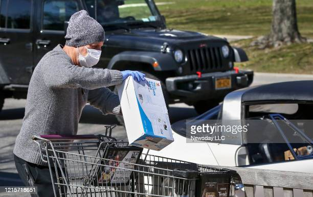 Wearing a mask and gloves Gordon Greenberg loads groceries into his car after shopping at the Stop Shop store in East Hampton on March 27 2020