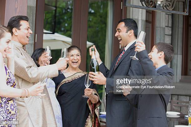 East Indian family celebrating with champagne