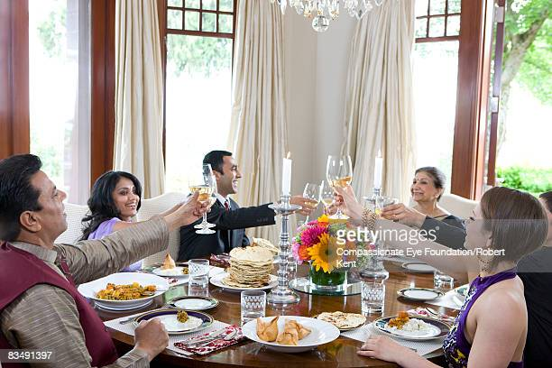 East Indian family making a toast at dinner table.