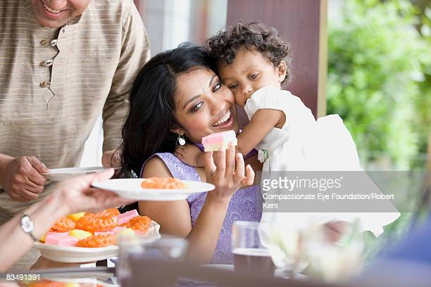 East Indian woman and child at family dinner.