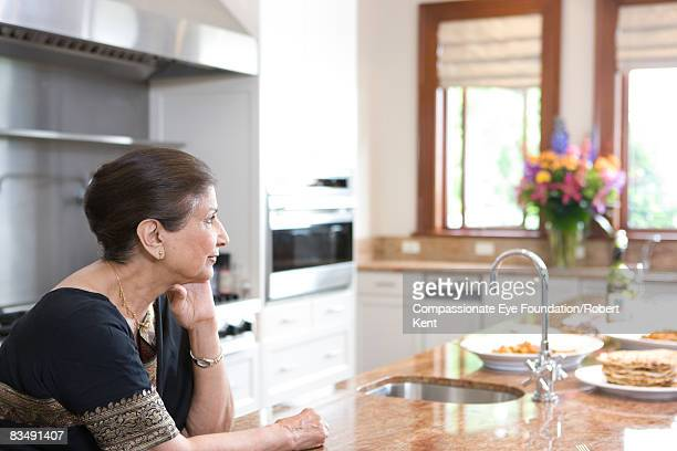 East Indian woman thinking in kitchen