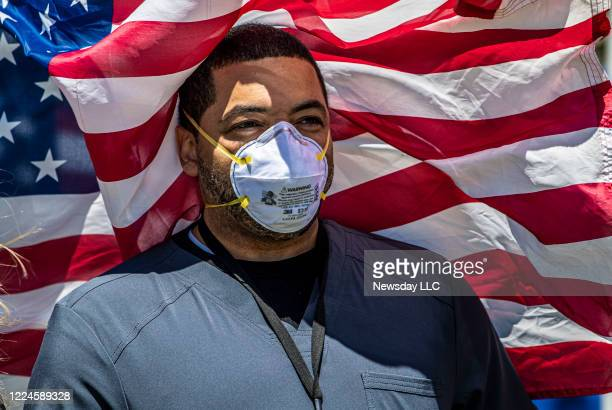 Derek Washington, a nurse at Nassau University Medical Center in East Meadow, New York, poses in front of one of dozens of American flags placed...