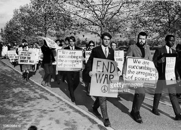 Picketers carry signs protesting the Vietnam War in Salisbury Park in East Meadow New York prior to the arrival of President Lyndon Johnson by...