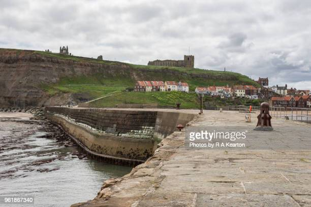 east pier at whitby harbour, north yorkshire, england - abby road stock photos and pictures