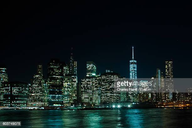 East River By Illuminated Modern City Against Clear Sky At Night