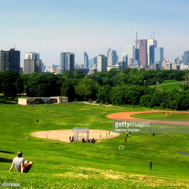 East Riverdale Park playground and Toronto skyline skyscrapers in distance on clear sunny day