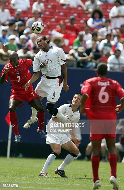 Panamanian Jorge Luis Dely Valdes and Oguchi Onyewu of the US jump for a header as teammate Jimmy Conrad and Panamanian Gabriel Gomez look on during...