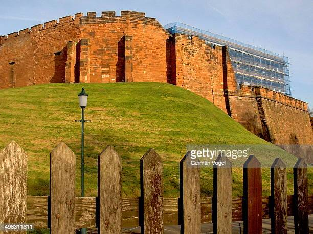 CONTENT] East section of the Chester city wall atop a green grass hill seen from a wooden fence by the promenade