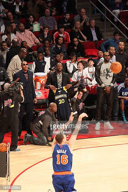 East Team Captain Dwyane Wade holds up Steve Novak's Marquette Jersey as Novak of the New York Knicks competes in the 2013 Foot Locker ThreePoint...